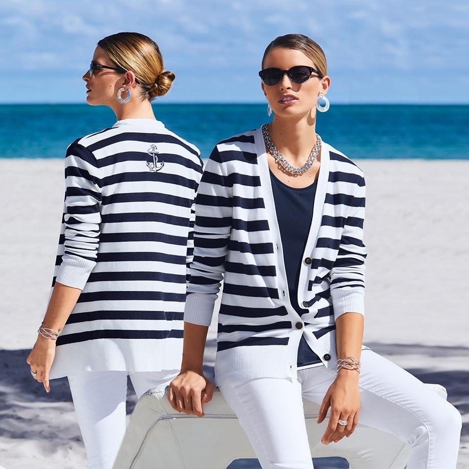 Zwei blonde Frauen mit Sonnenbrille und Ohrringen sitzend am Strand.