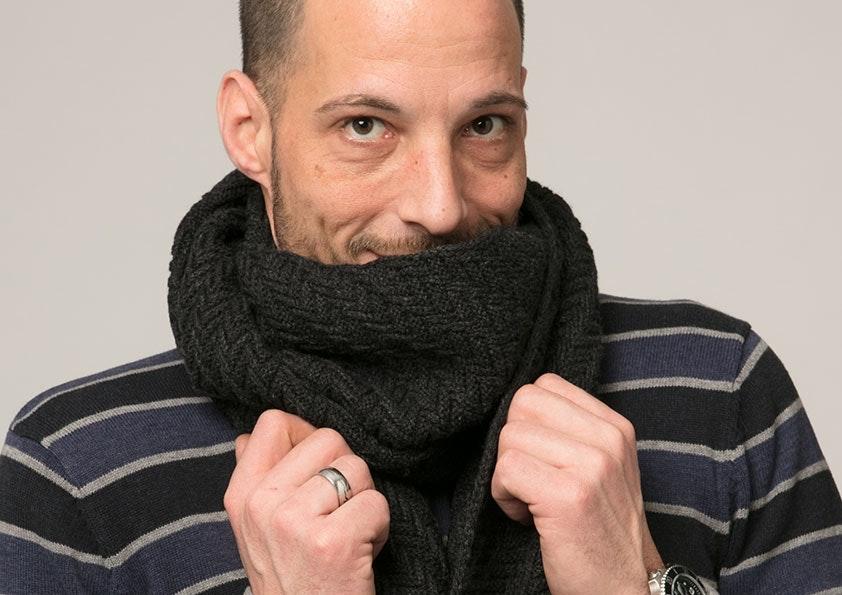 Mann mit braunen Augen versteckt sein Gesicht zur Hälfte unter einem schwarzen Schal. Er trägt einen gestreiften Pullover.