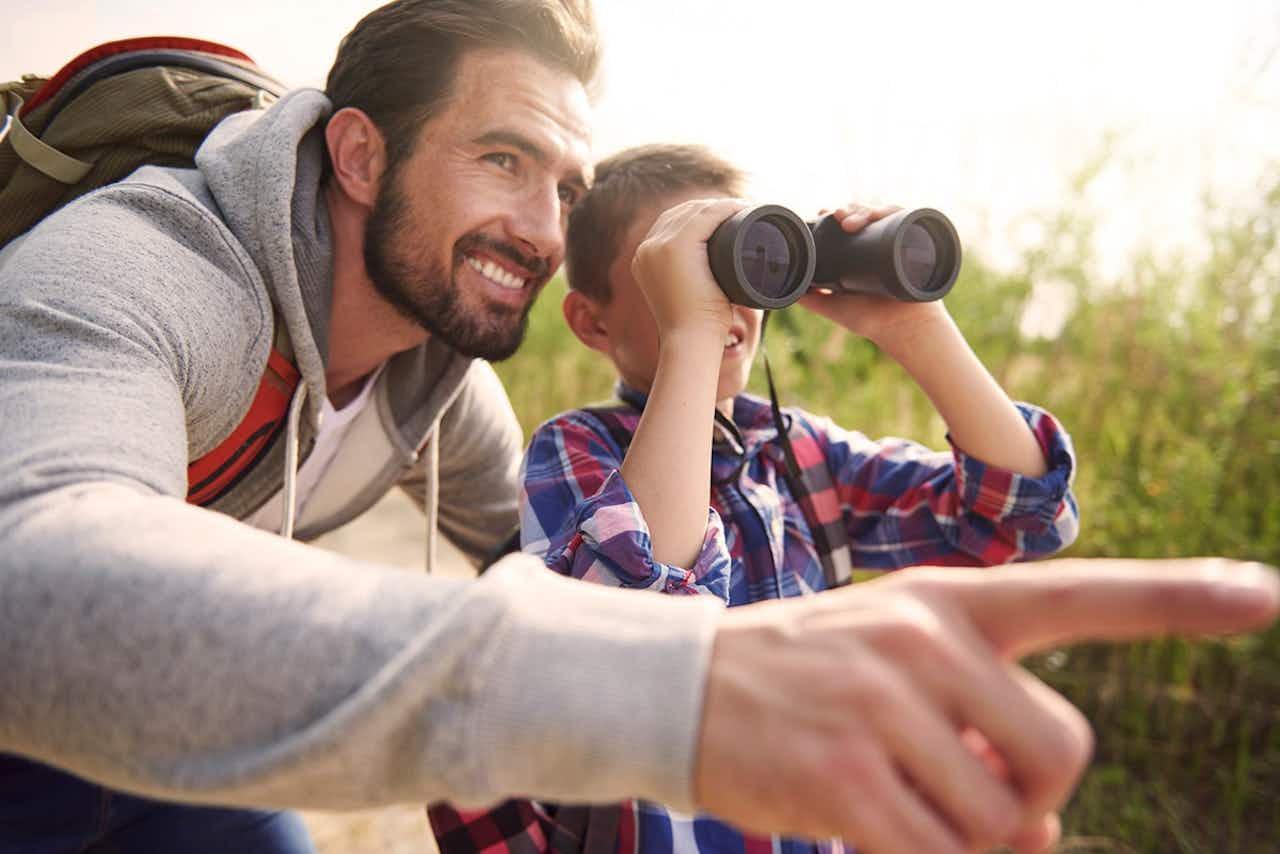Vater und Sohn mit Fernglas beim Wandern