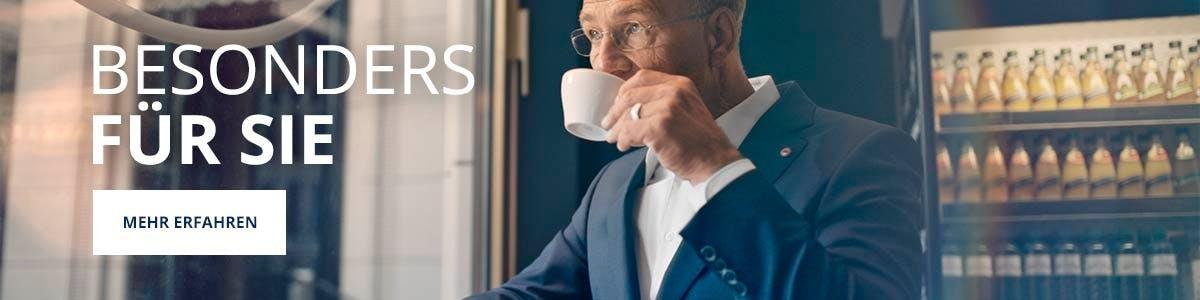 Mann in Anzug und Hemd trinkt aus einer Tasse, neben ihm ein Schriftzug.