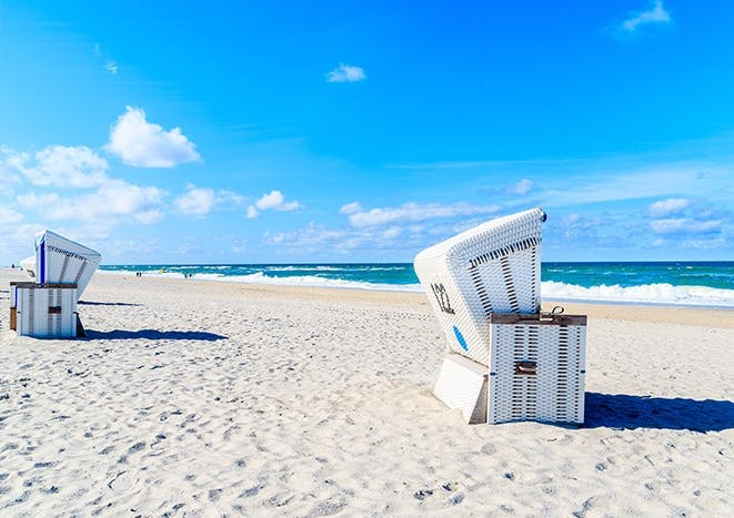 Strandkörbe auf Sand vor einem blauen Ozean.