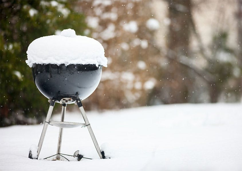 Ein schwarzer Kugelgrill ist mit Schnee bedeckt. Er steht auf einer Schneefläche, verschwommene Äste im Hintergrund.