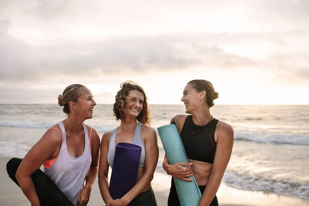 Frauen machen Yoga am Strand