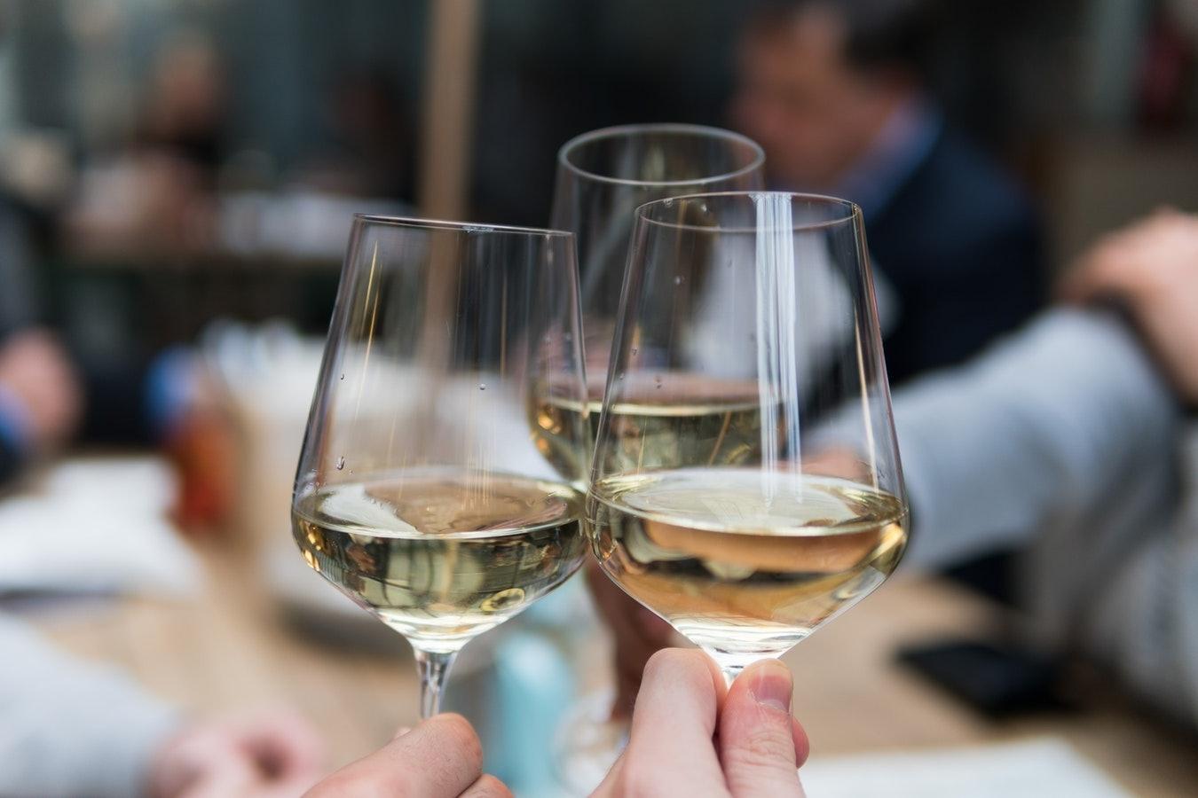 Drei Weingläser beim Anstoßen