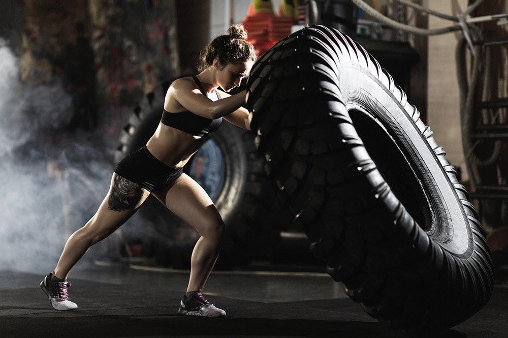 Junge Frau beim Tire Workout Crossfit