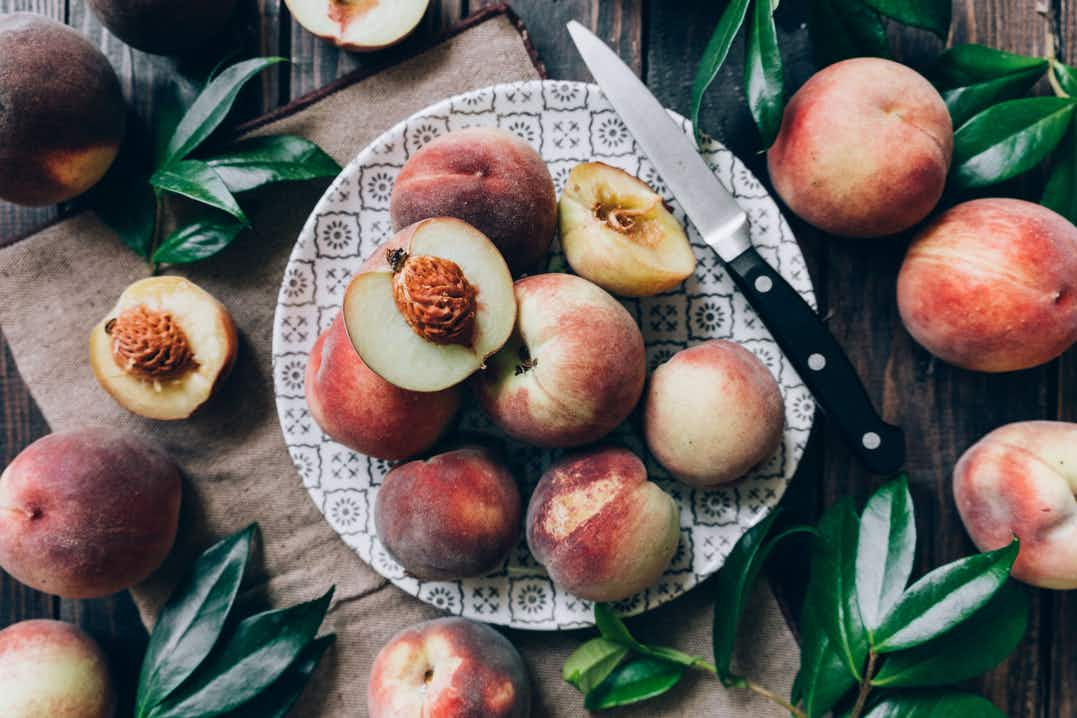 Freshly picked whole and halved peaches sitting on a patterned plate and sprawled across a wooden table