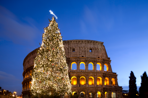Colosseum in Rome at twilight with a lit up Christmas tree in the foreground and two Cypress trees to the right of the Colosseum