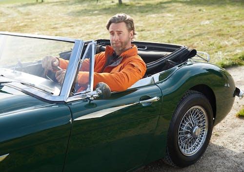 Mann fährt in grünem Oldtimer-Cabrio