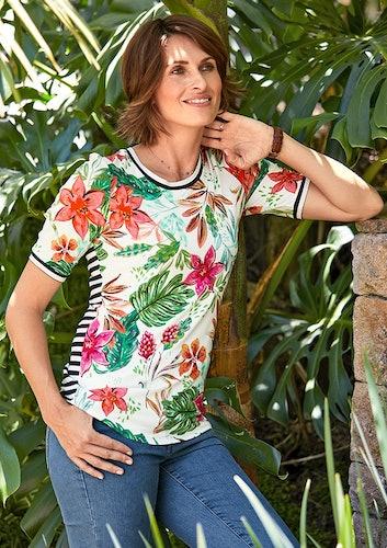 Frau in Jeans und weißem Shirt mit Blumenprint lehnt an einer Steinwand. Im Hintergrund grüne Palmenblätter.