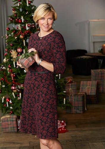 Blonde Frau im Kleid sthet vorm Weihnachtsbaum.