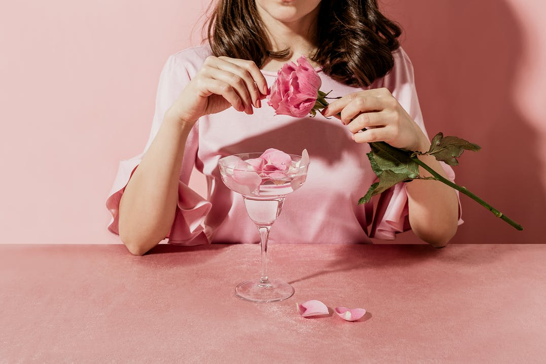 Brunette woman picking petals from a pink rose and placing them in an elaborate shaped glass of water. Everything is pink.