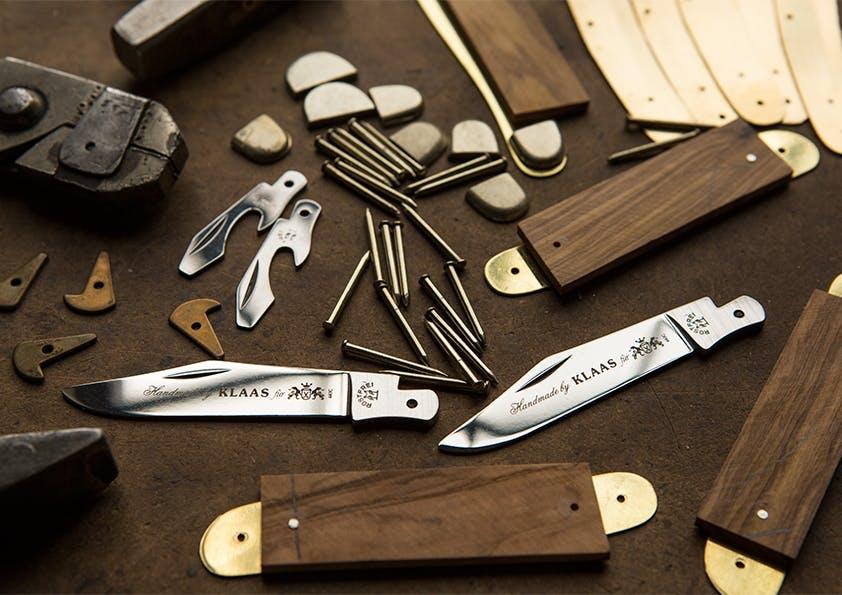 Silberne Messerklingen und Holzgriffe liegen zwischen Nadeln auf einem Tisch.