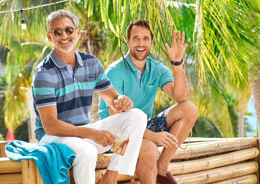 Zwei lachende Männer im Polo-Shirt sitzen auf einer Bank, einer winkt.