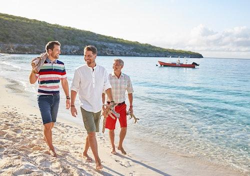 Drei Männer am Strand in kurzer Hose.