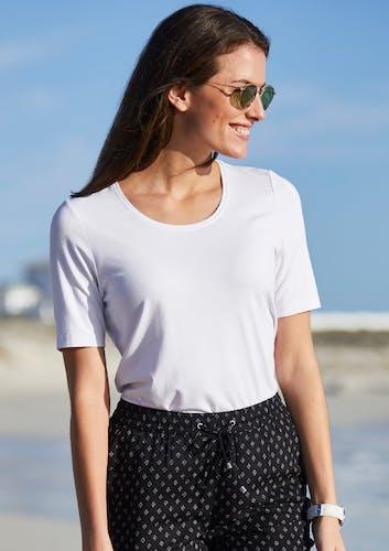 Frau am Strand_weißes T-shirt_dunkle Hose