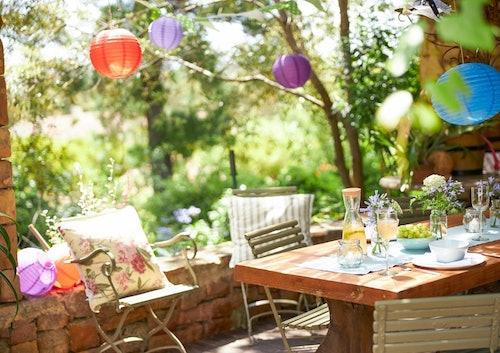 Schön eingedeckter Gartentisch mit bunten Lampions