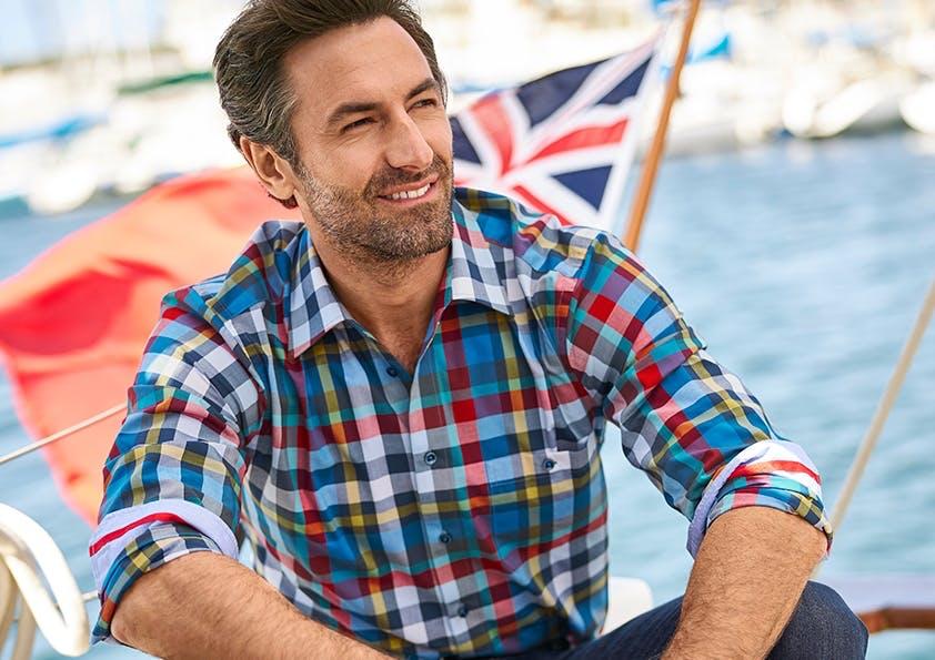 Mann auf Boot in Karo-Hemd