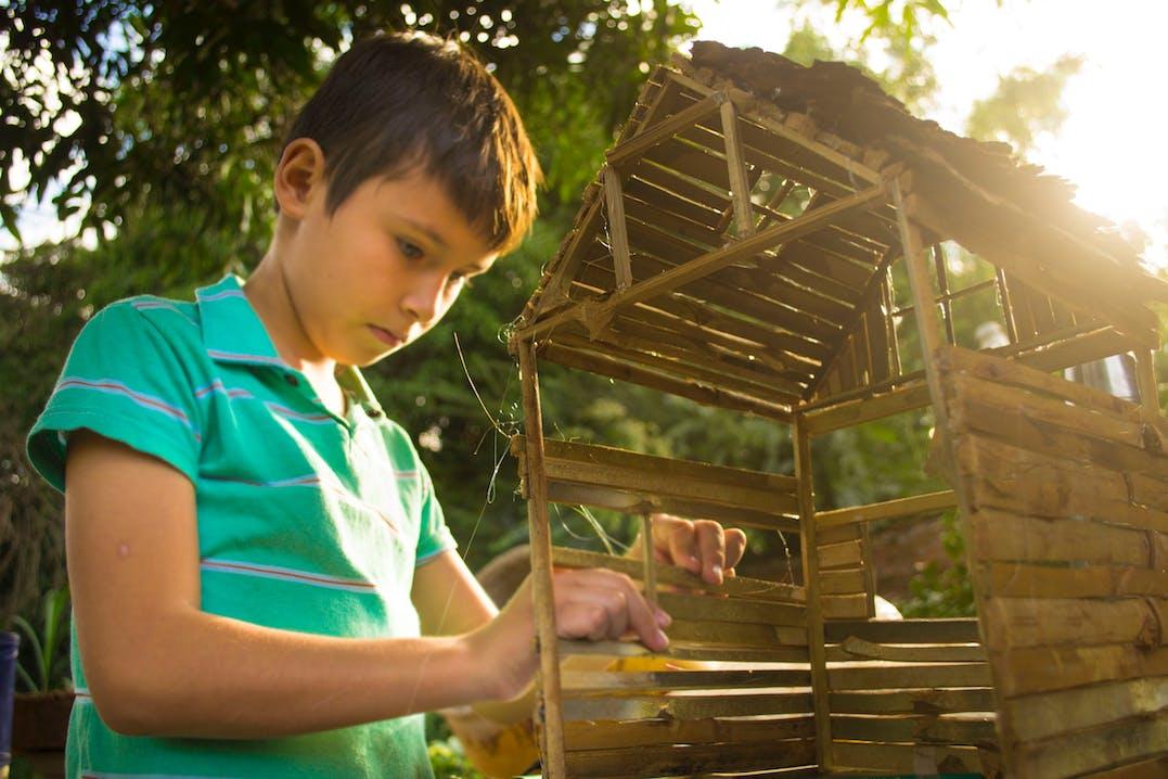 Junge baut an einem Bambushaus