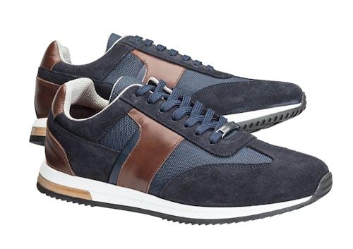 Blaue Sneaker mit braunen Details und Schnürsenkeln.