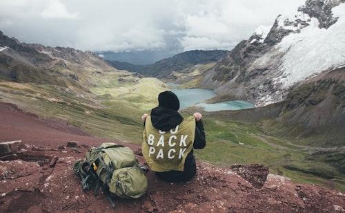 Ein Backpacker sitzt neben seinem Rucksack in den Bergen und schaut in ein Tal herab