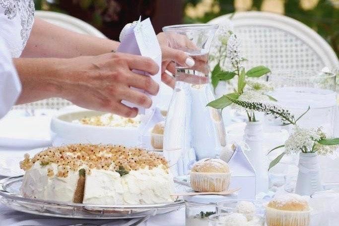 Eine im Garten gedeckte Kaffeetafel mit Kuchen und Wasserkarraffe.