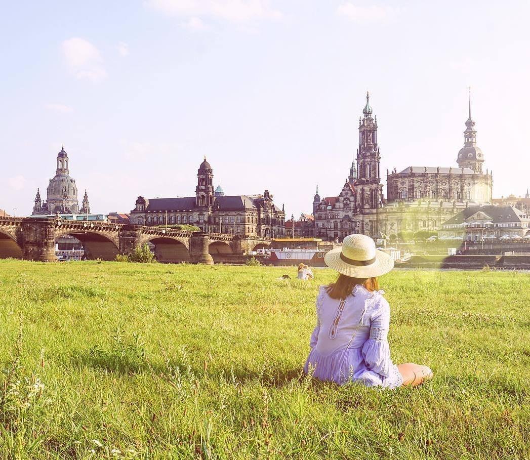 eine Frau mit Hut sitzt auf den Elbwiesen mit Blick aus die Dresdener Skyline