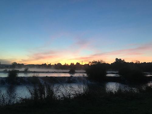 Gewässer mit dunklen Büschen. Darüber dunkelblauer Himmel mit orangenem Licht des Sonnenaufgangs.