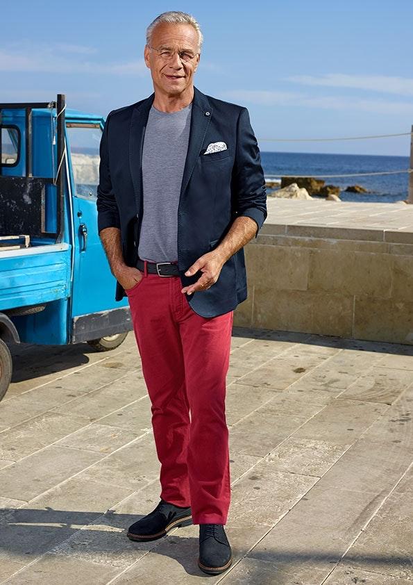 Mann trägt dunkelblaues Sakko und rote Chinohose, steht vor kleinem Lieferwagen, im Hintergrund ist das Meer zu sehen.