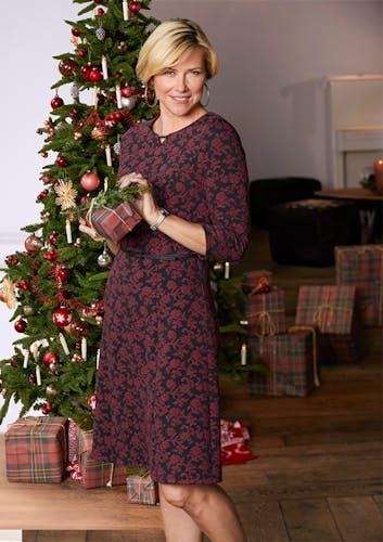 Blonde Frau in Kleid vor Weihnachtsbaum