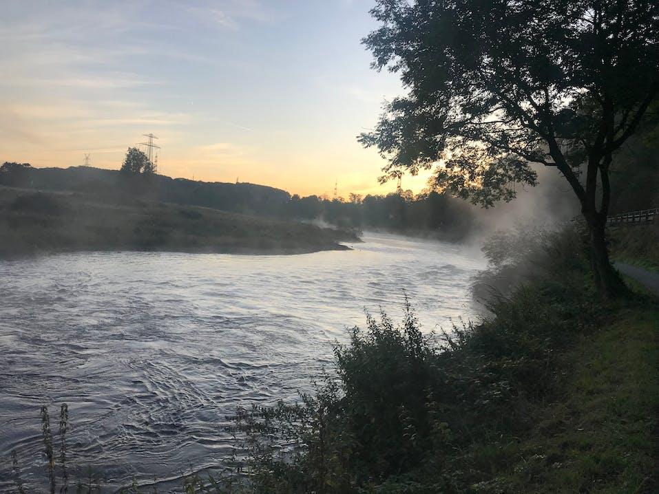 Fluss von Nebel umgeben mit Wiesenufer. Im Hintergrund blauer Himmel mit gelbem Licht.