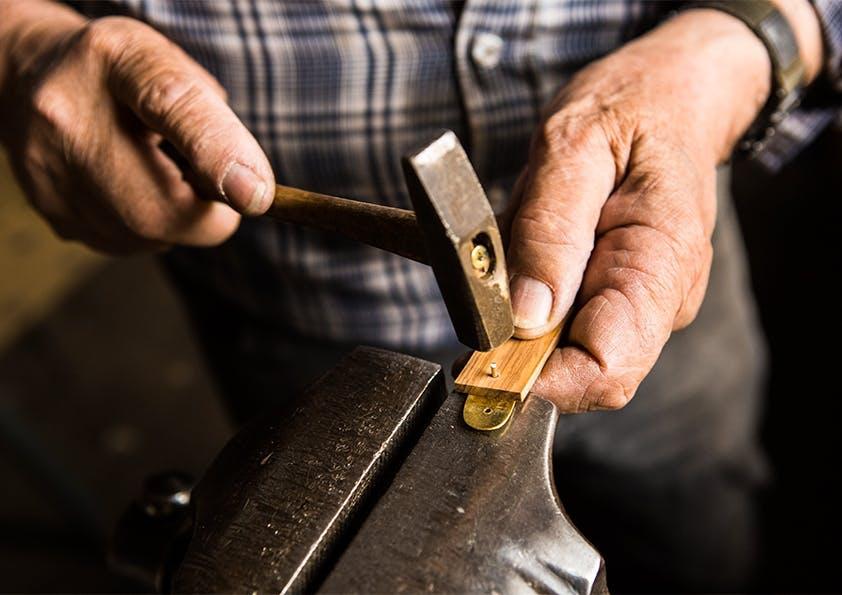 Männerhände halten einen Holzgriff und einen Hammer.