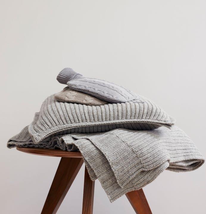 Flauschige Strick-Kissen und Decken für kuschelige Herbst-Abende.