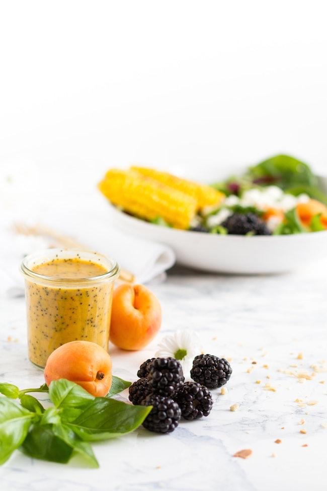 Auf einem Tisch mit weißer Tischdecke liegen Obst, Salat und ein Glas mit selbstgemachtem Salatdressing