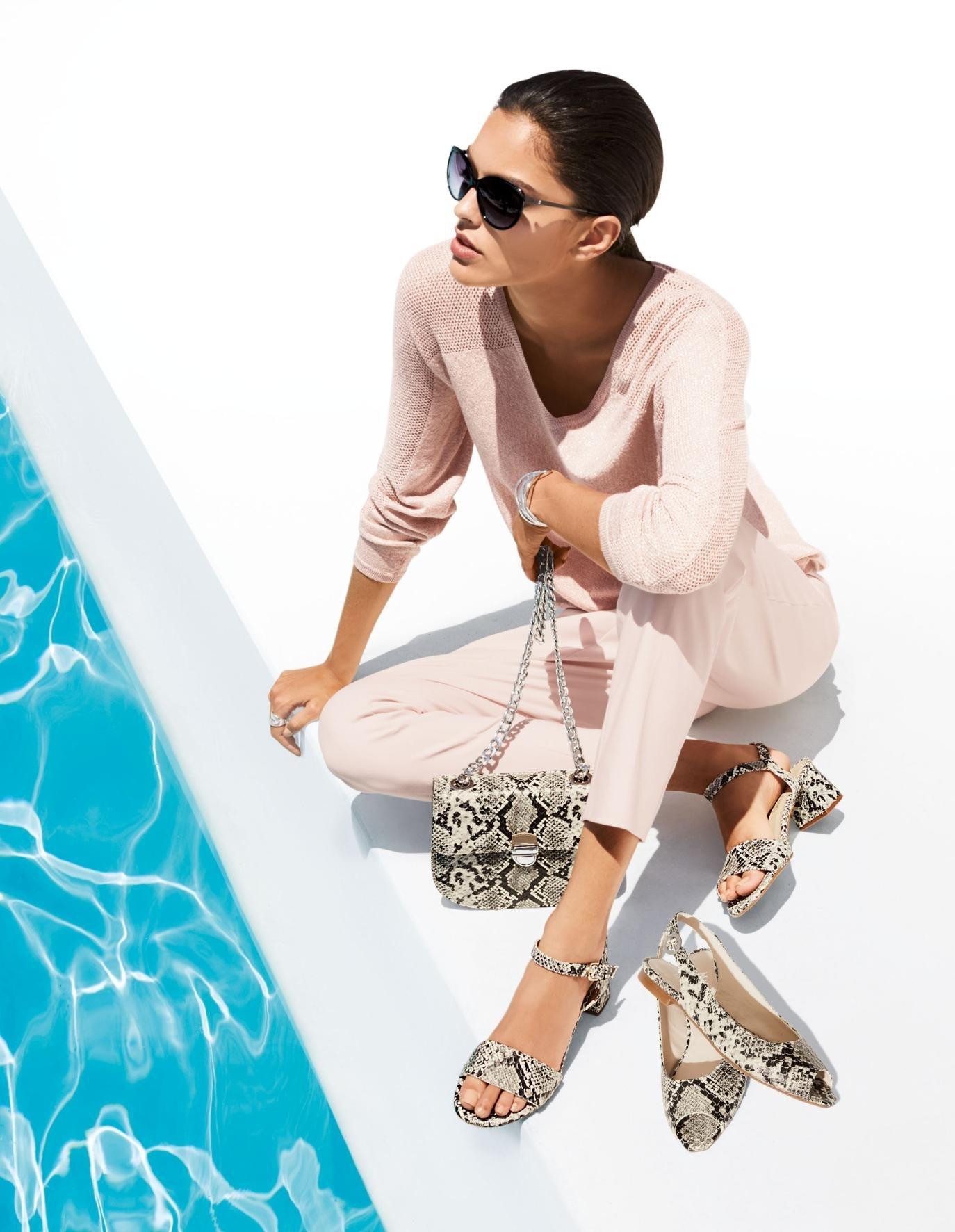 Frau am Pool sitzend mit Sonnenbrille und Handtasche