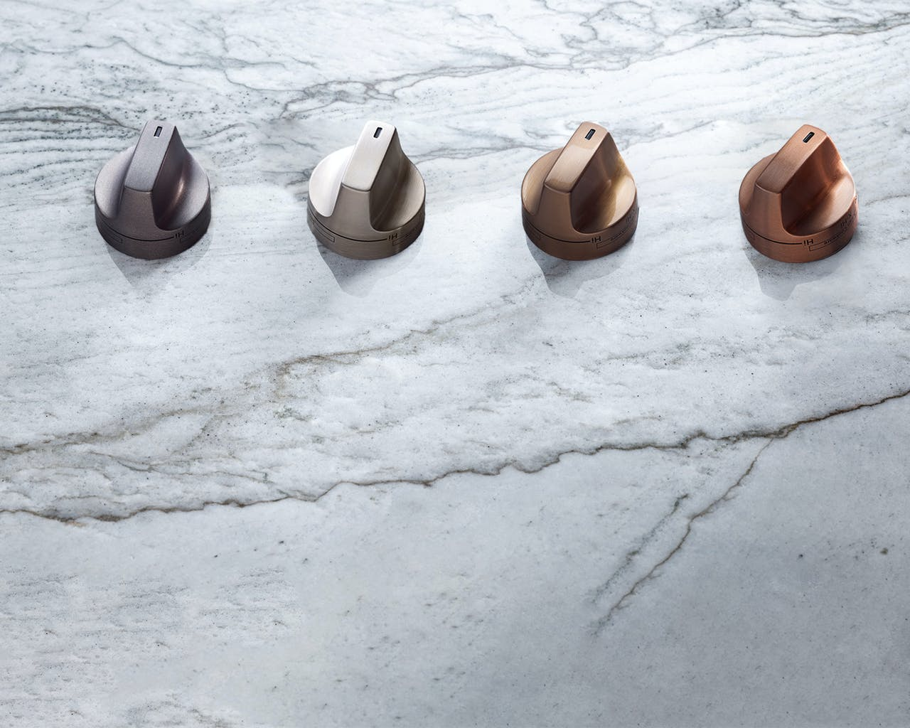 4 knobs on marble background. brushed black, brushed stainless, brushed bronze, brushed copper.