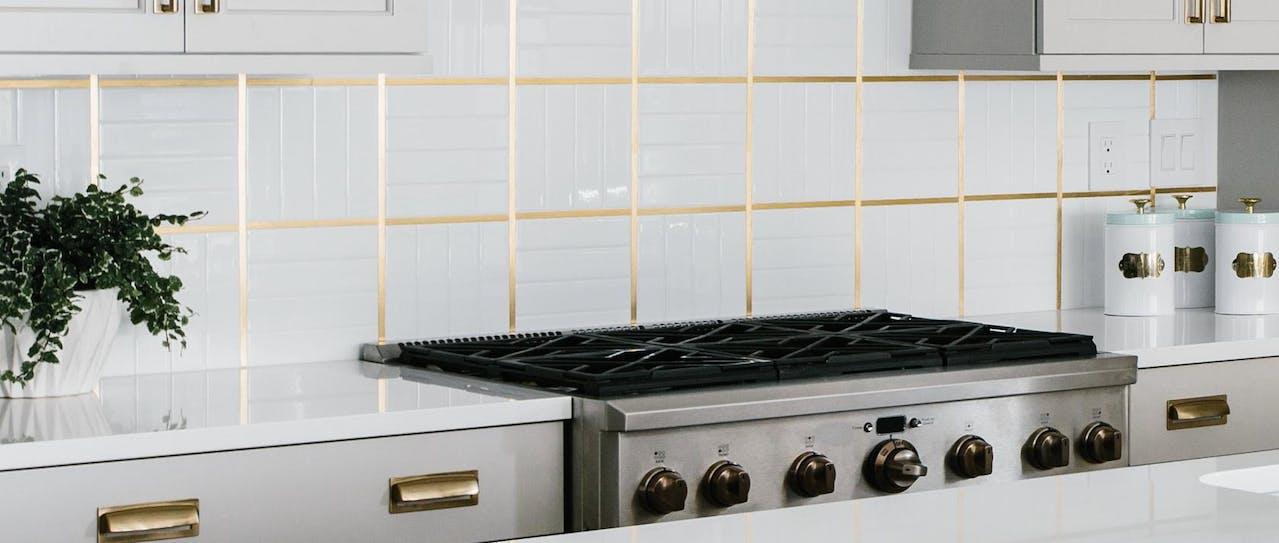 white tile backsplash with gold details
