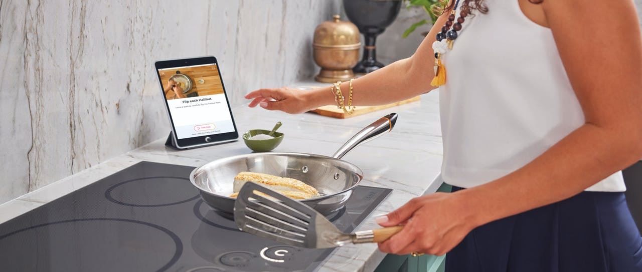 Woman cooking with Hestan Cue on induction cooktop
