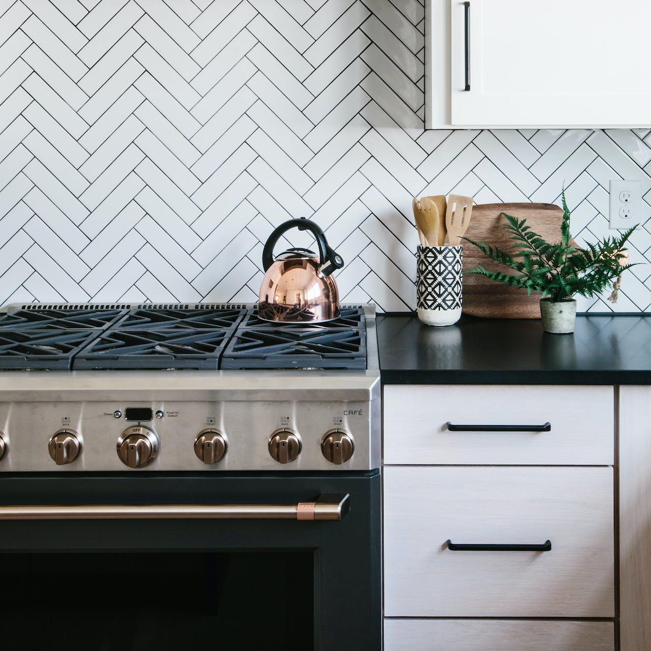 herringbone tile backsplash behind Cafe pro range