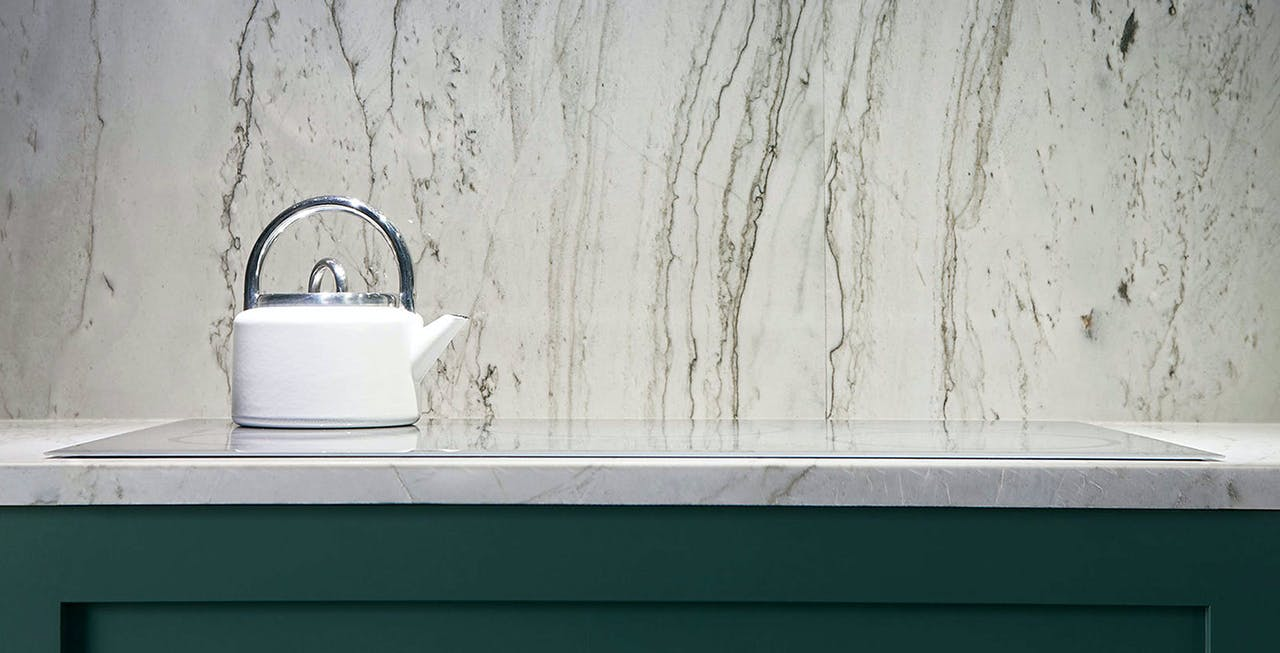 White tea kettle on glass cooktop with marble backsplash