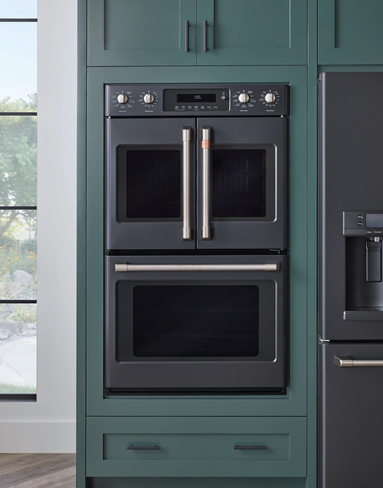 Matte black wall oven in green cabinets