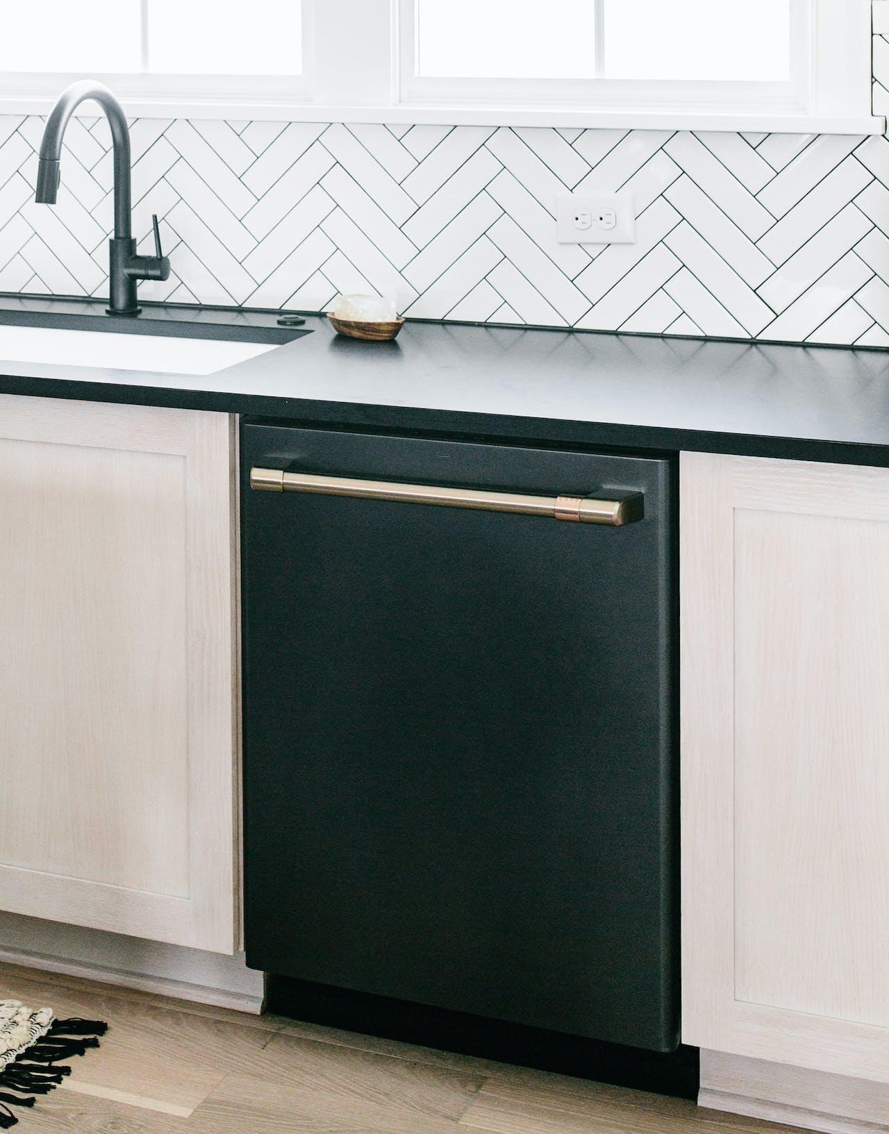 matte black dishwasher installed with chevron tile backsplash