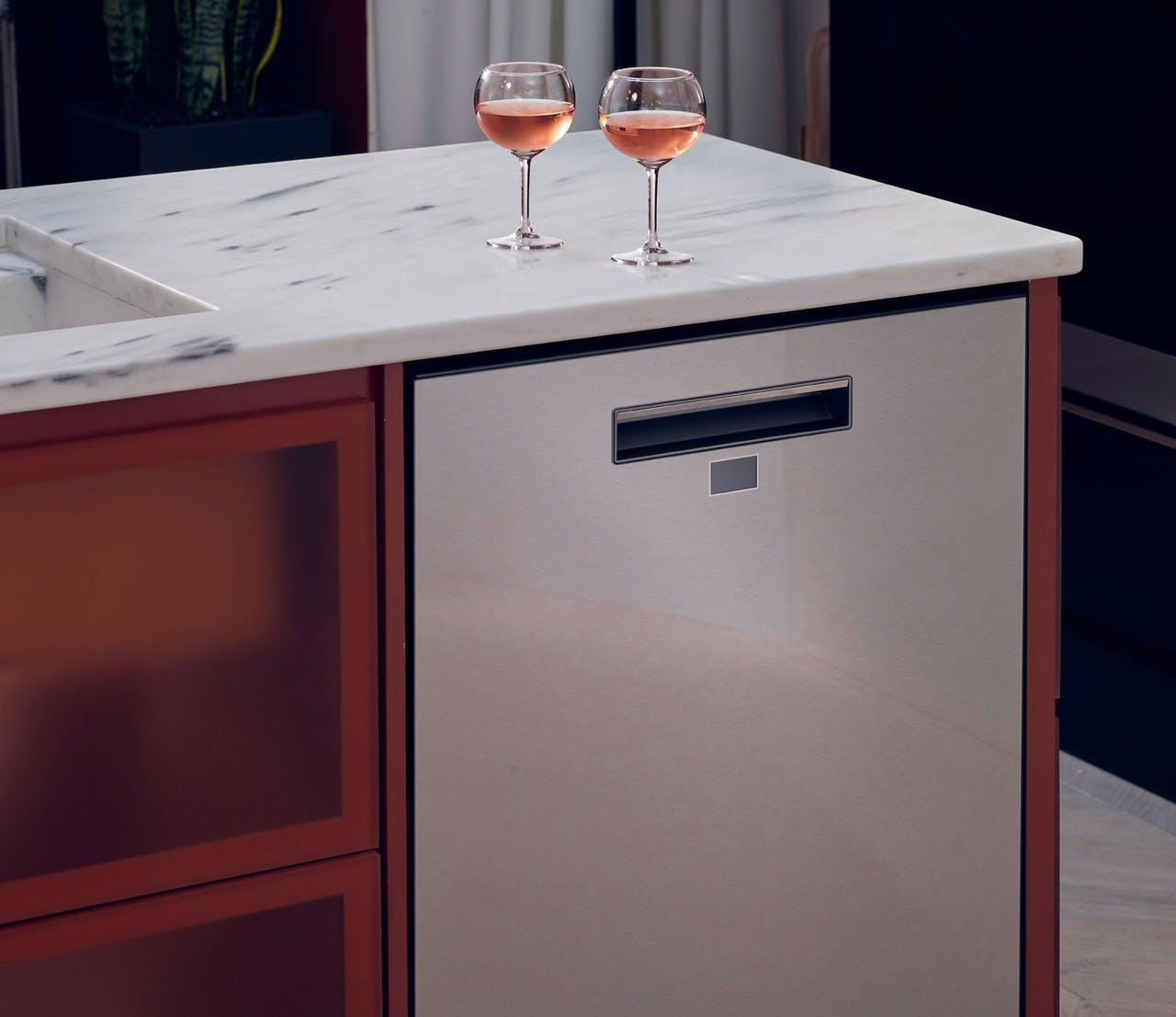 Modern Glass dishwasher with wine glasses above on counter