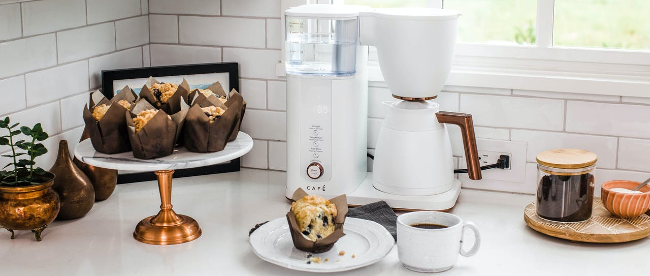 Matte white cafe coffee maker on counter with blueberry muffin
