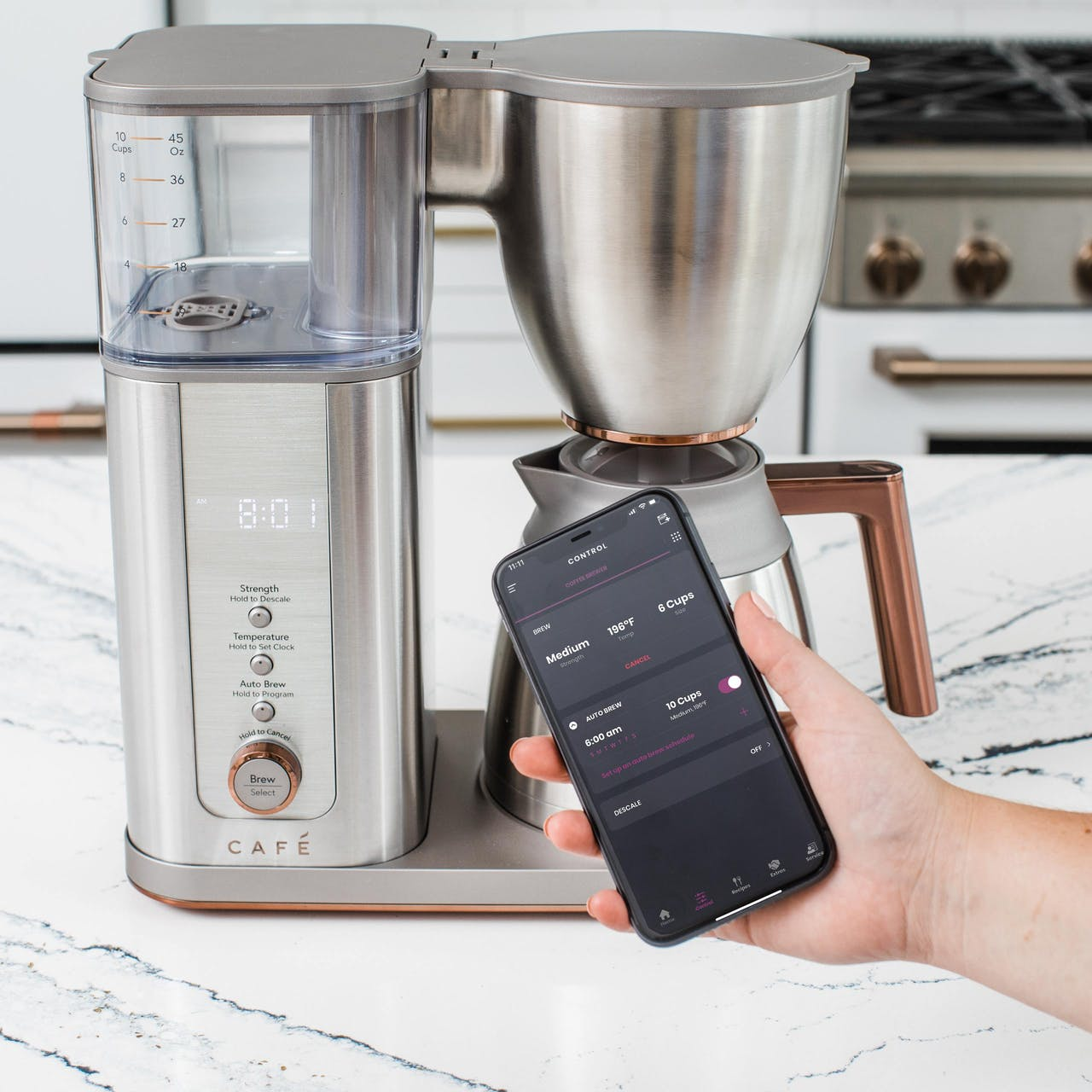 hand holding phone in front of stainless café coffee maker showing smartHQ app