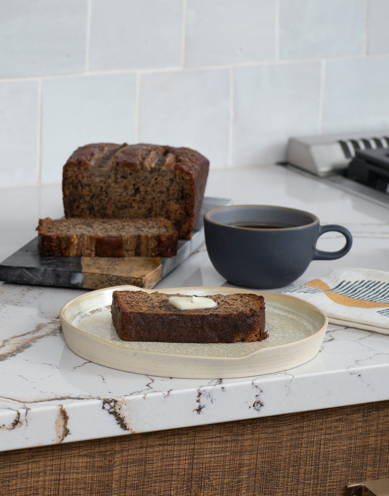 loaf of banana bread and cup of coffee on counter