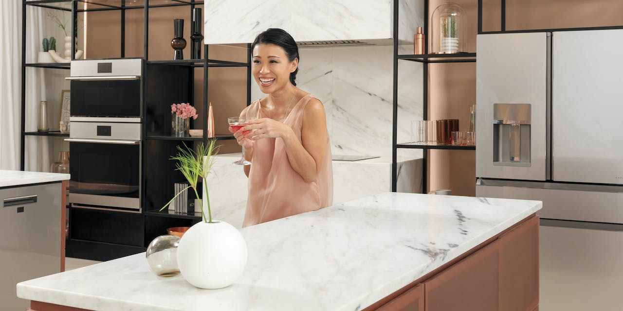 woman in kitchen with modern glass appliances