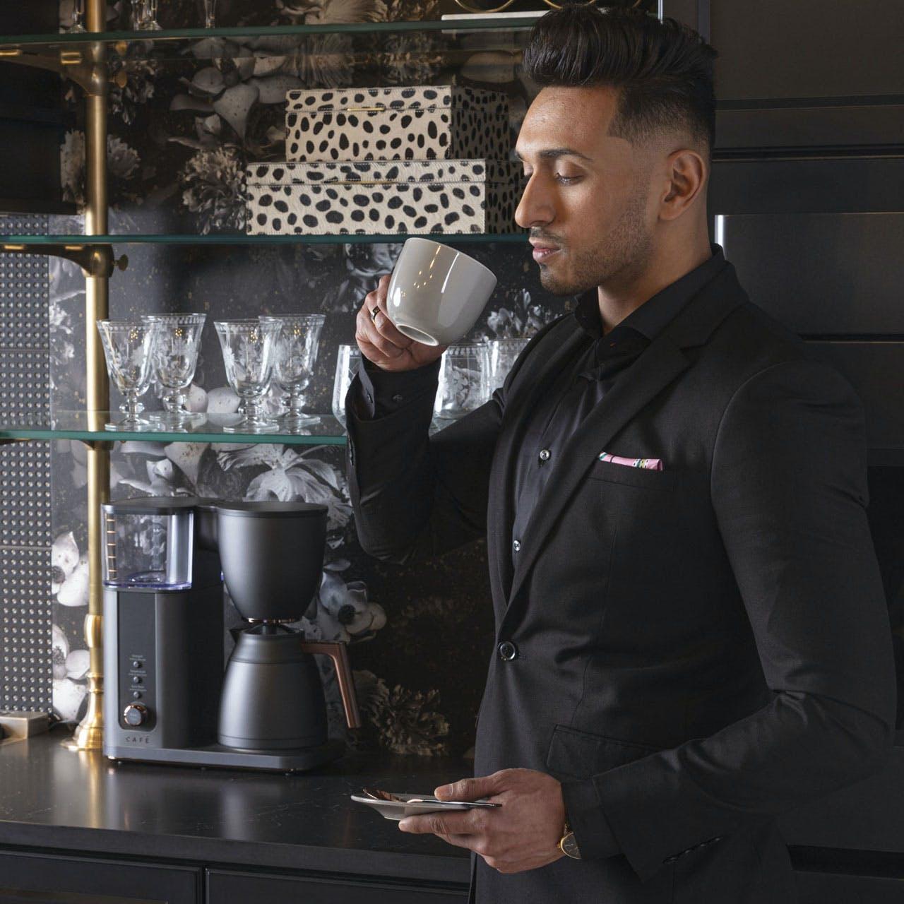 man drinking coffee in front of matte black coffee maker