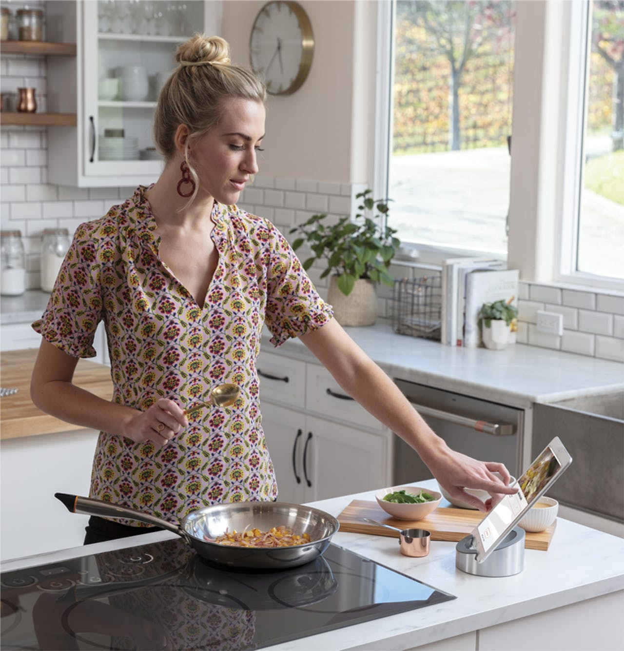Woman cooking with a hestan cue smart pan on Café induction cooktop