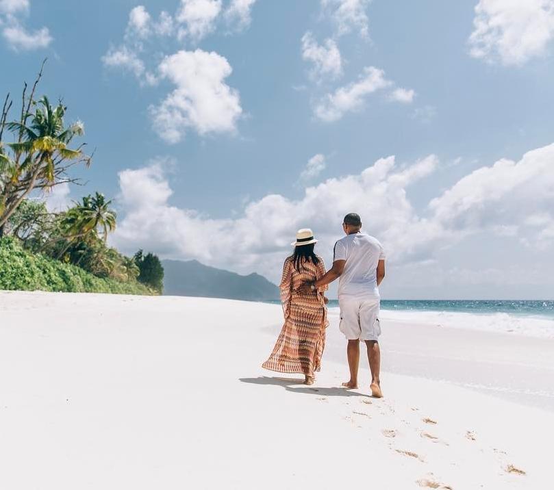 Pärchen läuft am Strand durch den Sand. Palmen säumen den weißen Sandstrand.