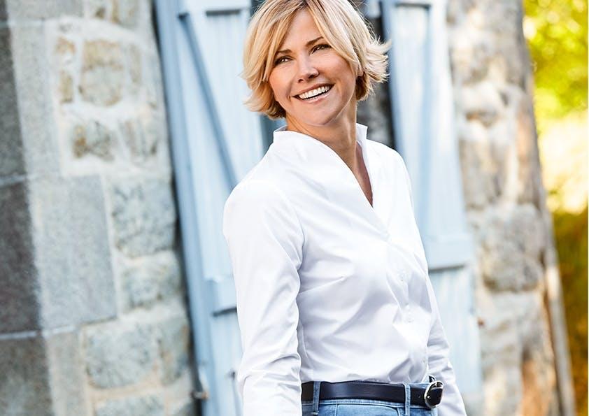 Frau mit kurzen blonden Haaren, weißer Bluse, Gürtel und Jeans lächelt.